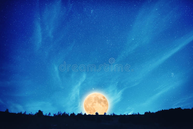 Full moon at night on the dark blue sky. Rise on full moon at night on the dark blue sky with many stars and clouds stock images