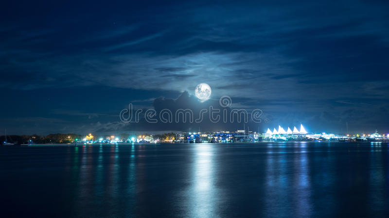 Full Moon Over Bright City. A full moon over a bright city landscape on a calm night stock photos