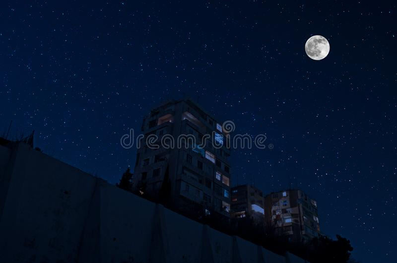 Full moon over the city at night, Baku Azerbaijan. Big full moon shining bright over skyscrapers royalty free stock image