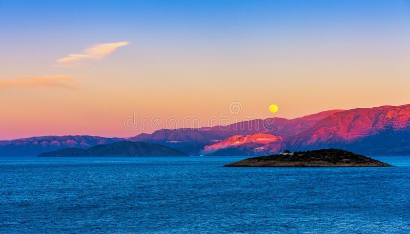 Full moon over Crete at sunset. Full moon over the island of Crete at sunset, Mirabello Bay, Crete, Greece stock photos
