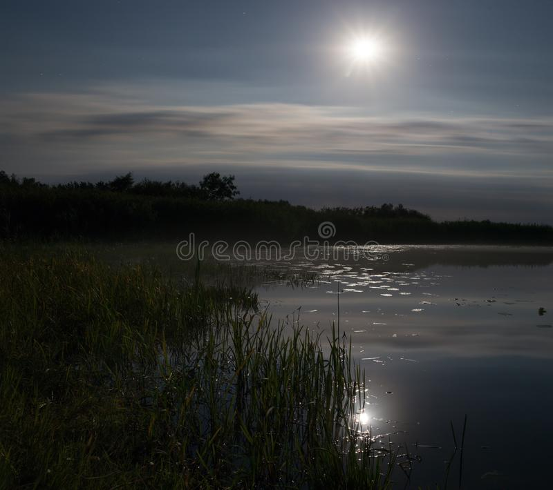 Full moon over foggy river Stochid in Volyn. Moon light at night landscape. Summer night fishing time stock photo
