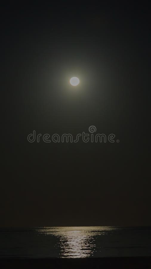 Full moon over the ocean with intensive light reflection royalty free stock photography