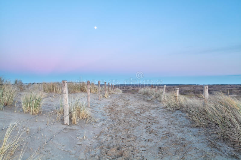 Full moon over sand path with fence in dunes royalty free stock photos
