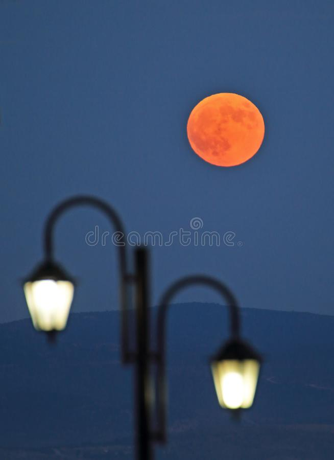 Full moon over street lamp stock photo