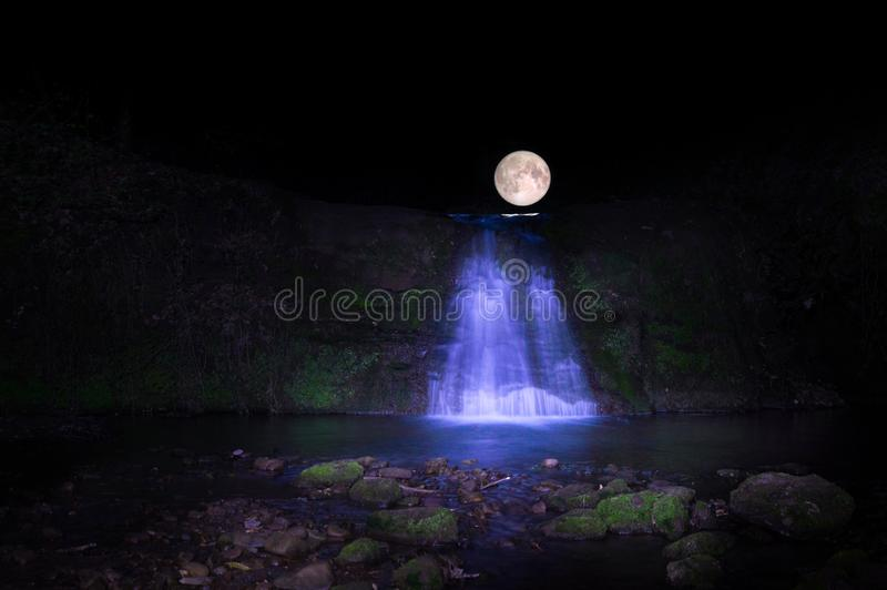 Full moon over water fall stock image