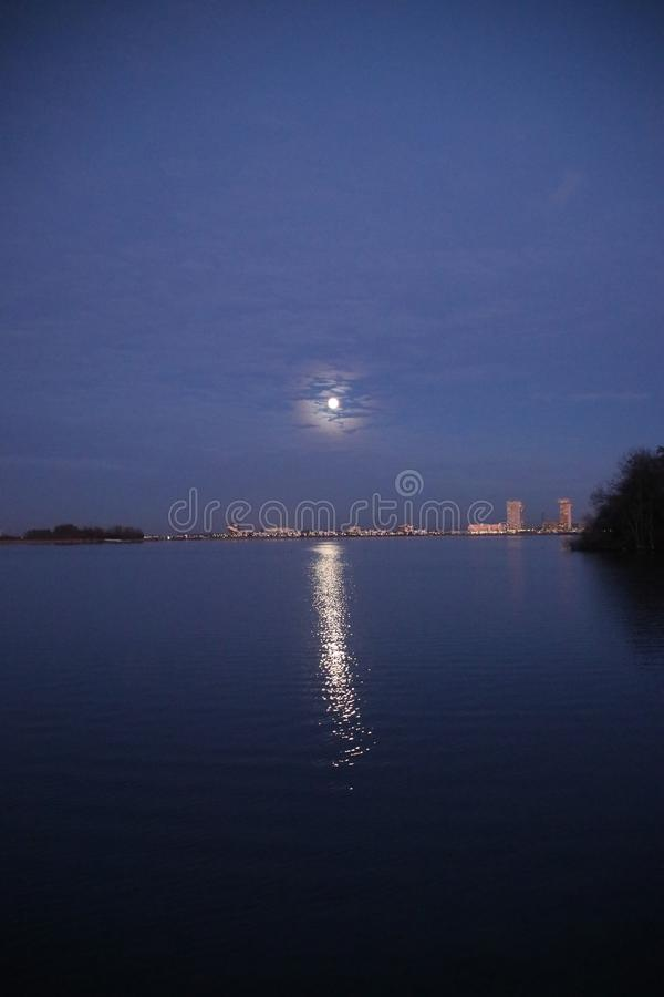 Full moon is rising above Nesselande beach reflecting on the Zevenhuizerplas as seen at Oud Verlaat just after sunset. stock photo