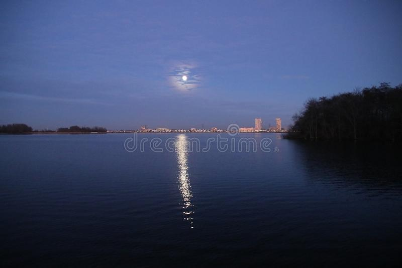 Full moon is rising above Nesselande beach reflecting on the Zevenhuizerplas as seen at Oud Verlaat just after sunset. royalty free stock images