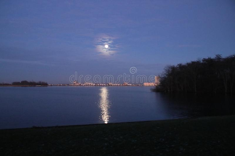Full moon is rising above Nesselande beach reflecting on the Zevenhuizerplas as seen at Oud Verlaat just after sunset. stock photos