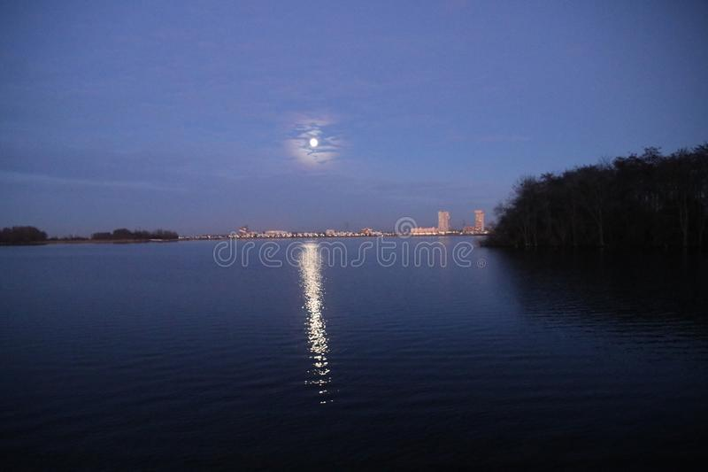 Full moon is rising above Nesselande beach reflecting on the Zevenhuizerplas as seen at Oud Verlaat just after sunset. stock images