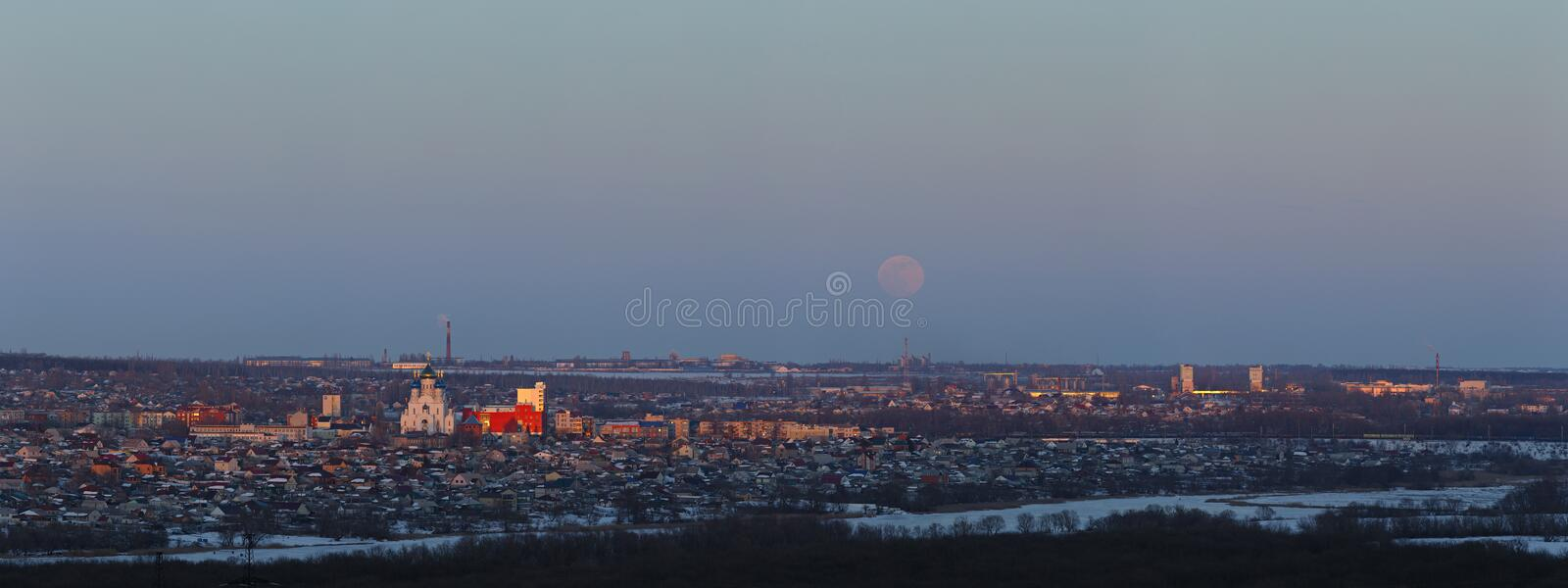 Full moon rising over the city. Sunset time in the twilight sky. Panoramic view of the Orthodox Church.  royalty free stock images