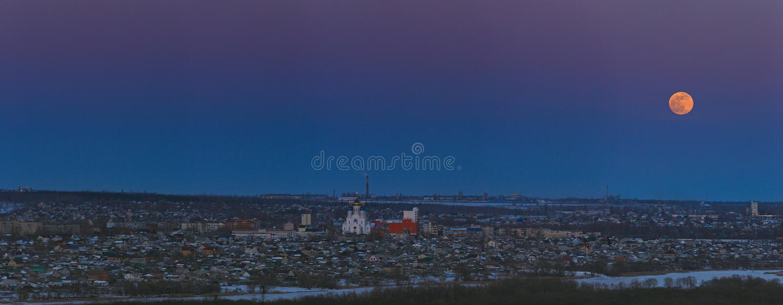 Full moon rising over the city. Sunset time in the twilight sky. Panoramic view of the Orthodox Church.  stock image