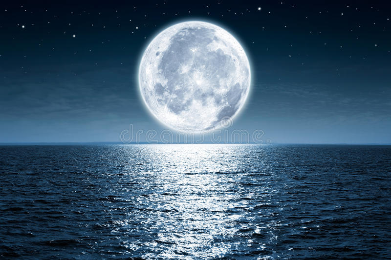 Full moon. Rising over empty ocean at night with copy space
