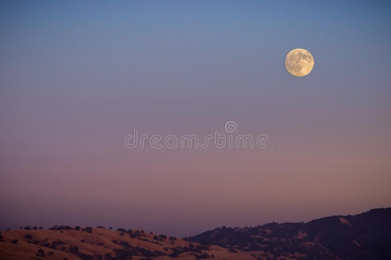Full moon rising over a mountain ridge. Colorful sky background, San Francisco bay, California stock photos