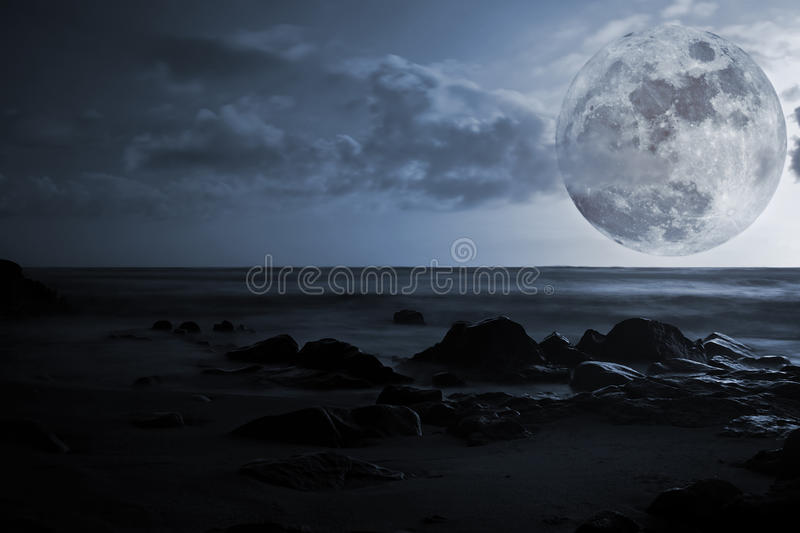 Full moon, sea and glowing rocks. Composition with full moon, sea and glowing rocks royalty free stock photo