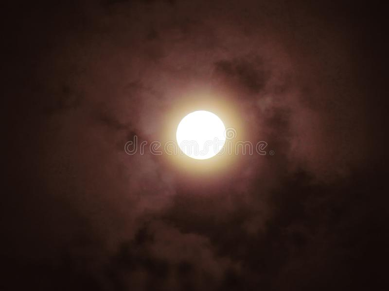 Full moon shining on the clouds. Dramatic scence royalty free stock photography