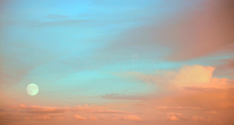Full moon at sunset. With rose and peach coloured clouds against blue turquoise sky stock images