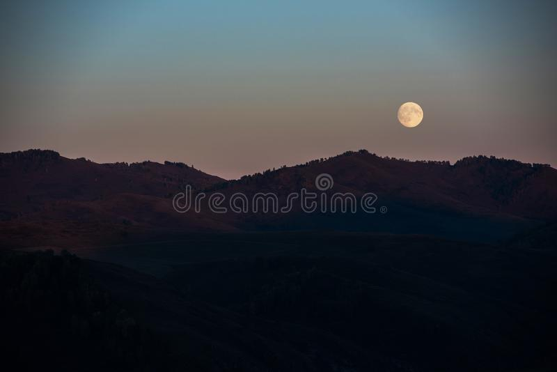Full moon at sunset. In Altai Mountains stock image