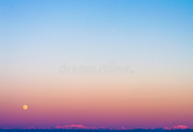 Full moon Sunset in Japan. The golden moon, and the strong pink to blue sky shading with no clouds stock photography