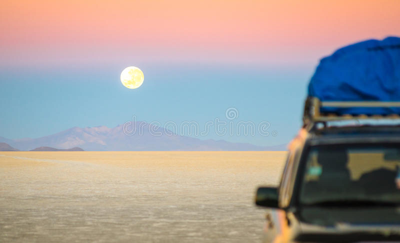Full moon sunset on Salar De Uyuni - Bolivia. Full moon sunset with off road jeep vehicle on Salar De Uyuni - World famous nature wonder place in Bolivia stock photos