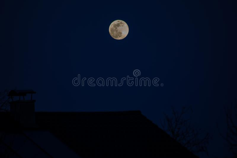 Full Moonrise in spring. Full moon rising over a house a in Germany at the beginning of spring royalty free stock image