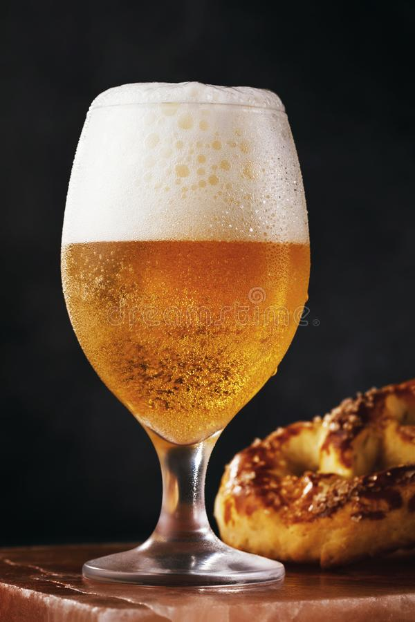 Full mug of filtered light beer with a salted pretzel on a stone stand royalty free stock images
