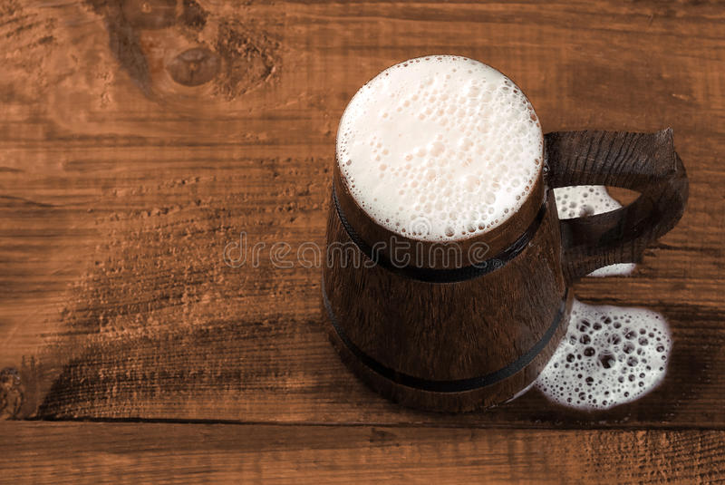 Full mug of fresh beer on a wooden table. stock photo