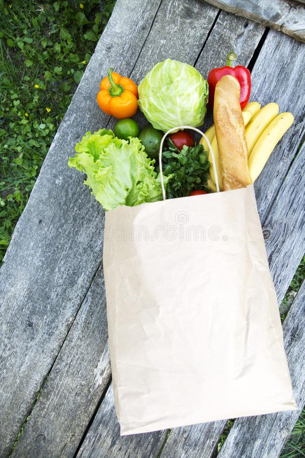 A full paper bag of healthy products on rustic wooden table, overhead view. From above, top view stock photo