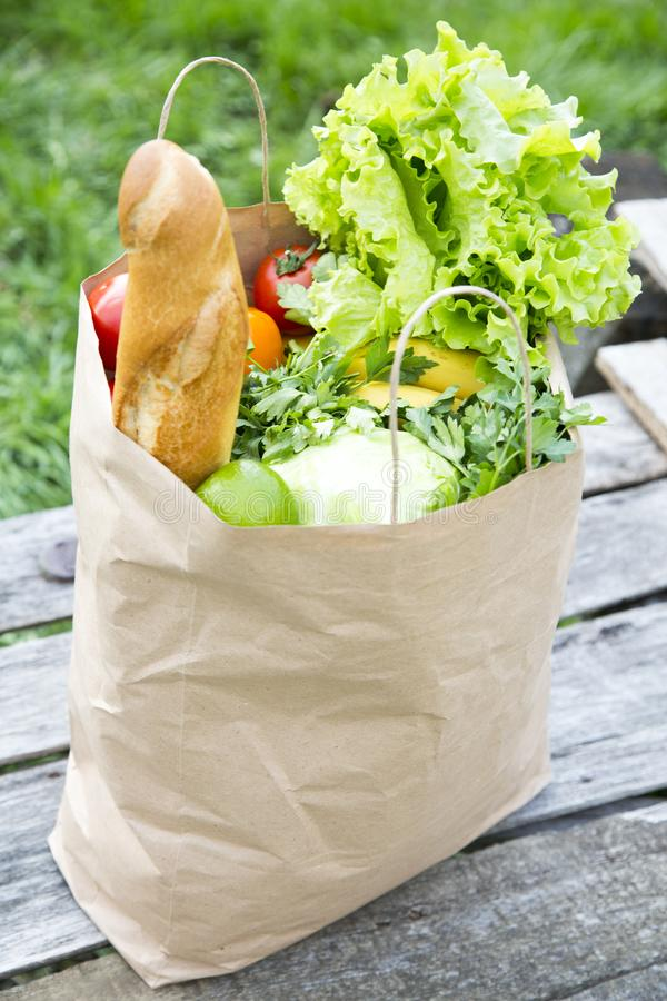 A full paper bag of healthy products stands on the wooden table. stock photo