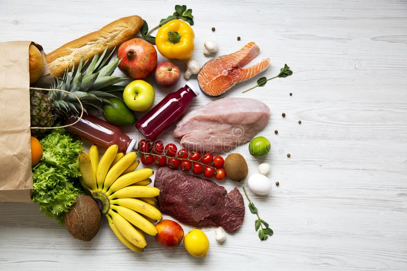 Full paper bag of healthy raw food on white wooden table. Cooking food background. Flat-lay of fresh fruits, veggies, greens, diff. Erent meat, top view, copy stock photo