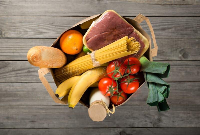 Full pappers- påse av olikt livsmedel på träbakgrund arkivbilder