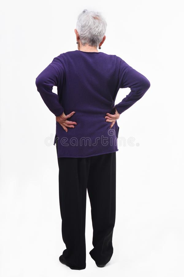 Full portrait of the back of an older woman with pain in the back on white background stock photos