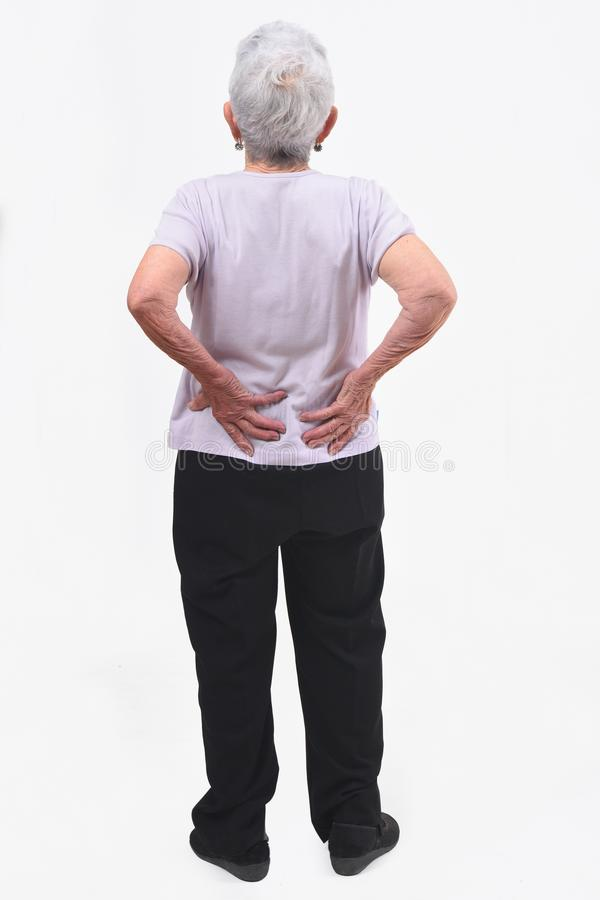 Full portrait of the back of an older woman with pain in the back on white background stock images