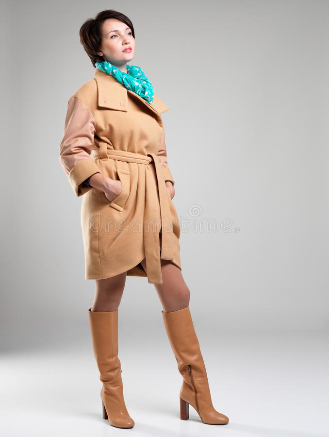 Full portrait of fashion woman in autumn coat with green scarf. Full portrait of fashion woman in beige autumn coat with green scarf at studio on grey background royalty free stock photos