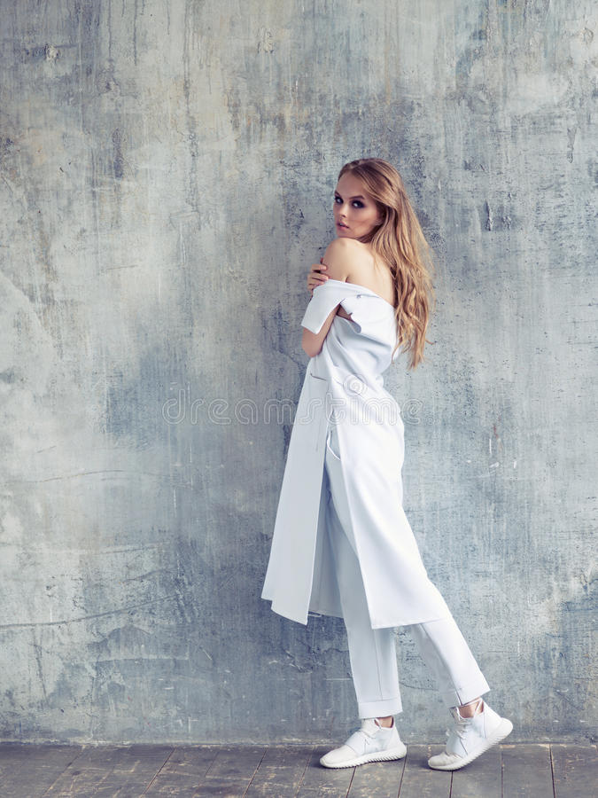 Full portrait of fashion woman wearing white design coat, trousers and sneakers. Fashion style shot royalty free stock photo