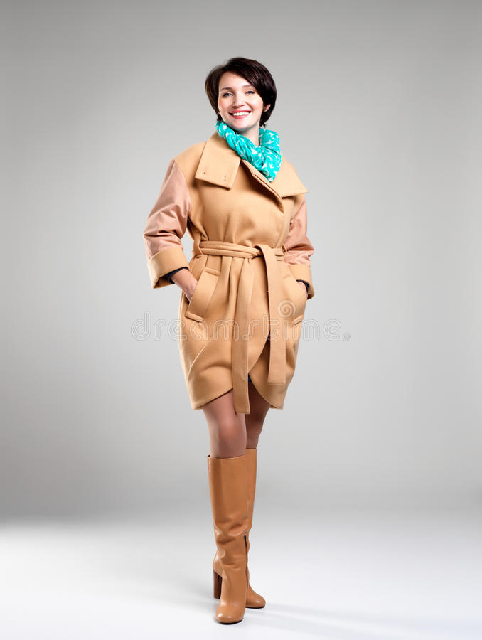 Full portrait of happy woman in autumn coat with green scarf. Full portrait of happy woman in beige autumn coat with green scarf at studio on grey background stock image