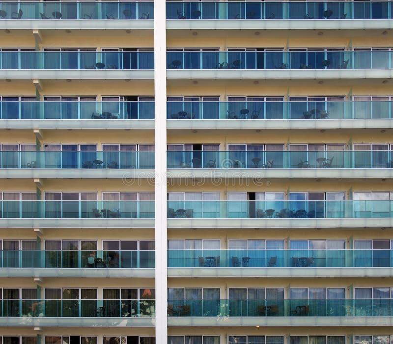 Full rambild av en stor lägenhetskomplex med geometriska rader av att upprepa fönster och balkonger med utvändigt möblemang arkivfoto