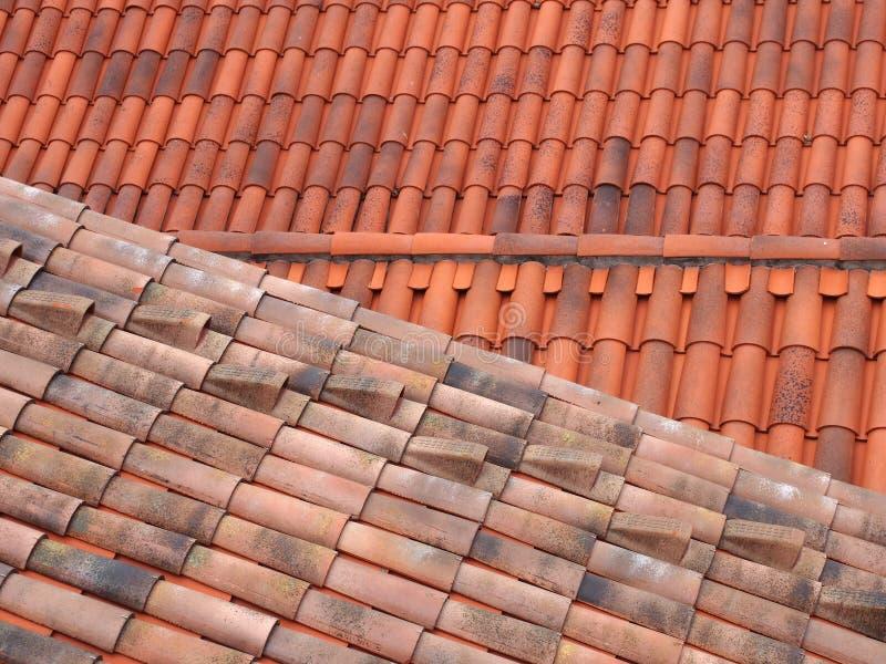 Full ramsikt av gamla och nya traditionella röda terrakottatak med krökta överlappande tegelplattor i överlappande linjer arkivfoton