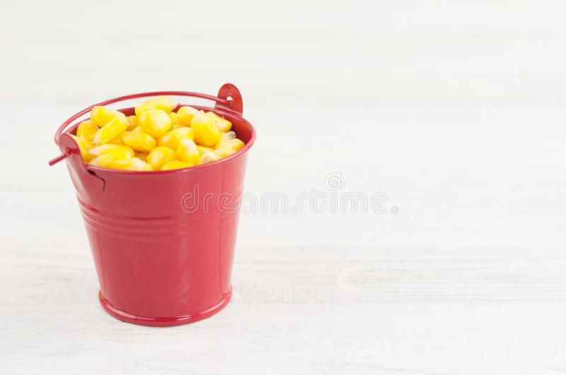 Full red metal bucket of grain of yellow ripe corn. On old rural white wooden planks stock image