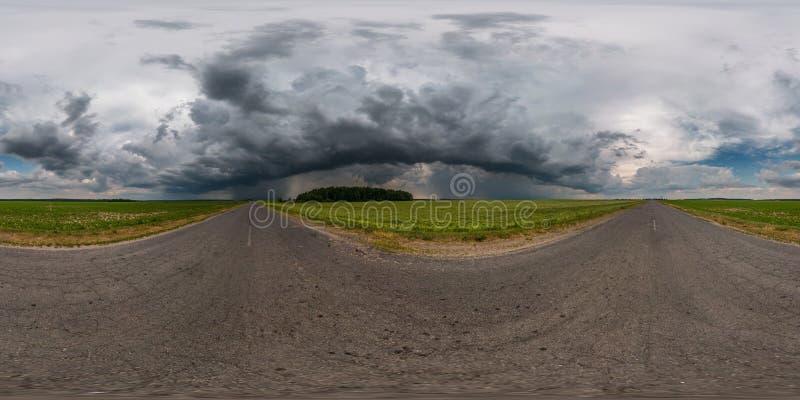 Full sömlös sfärisk hdrpanorama 360 grader vinkelsikt på asfaltvägen bland fält i afton med enorma svarta moln fotografering för bildbyråer