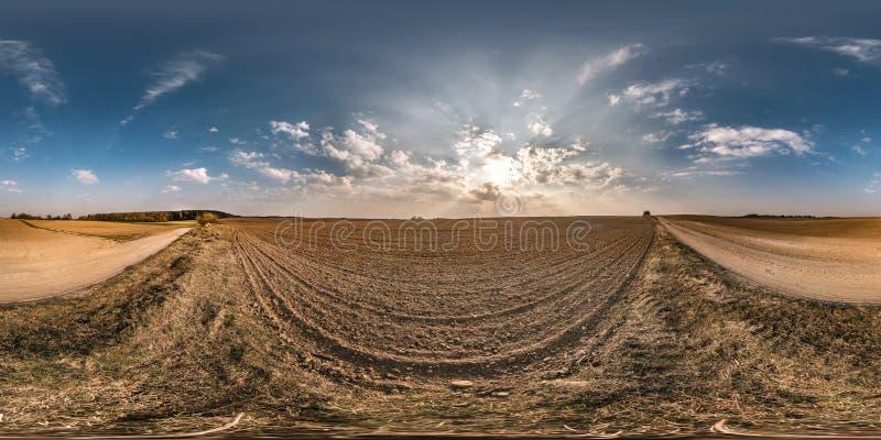 Full sömlös sfärisk panorama 360 grader vinkelsikt nära grusvägen bland ängfält i våraftonsolnedgång med enormt arkivbilder