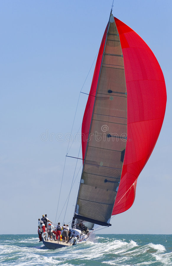 Full Sail Power. A fully crewed racing yacht with a red spinnaker catching the wind and leaving a big wake
