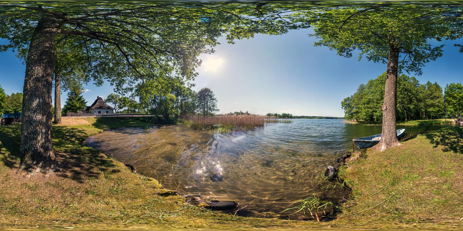 Full seamless panorama 360 by 180 angle view on the shore of huge forest lake with a boat in sunny summer day in equirectangular royalty free stock image