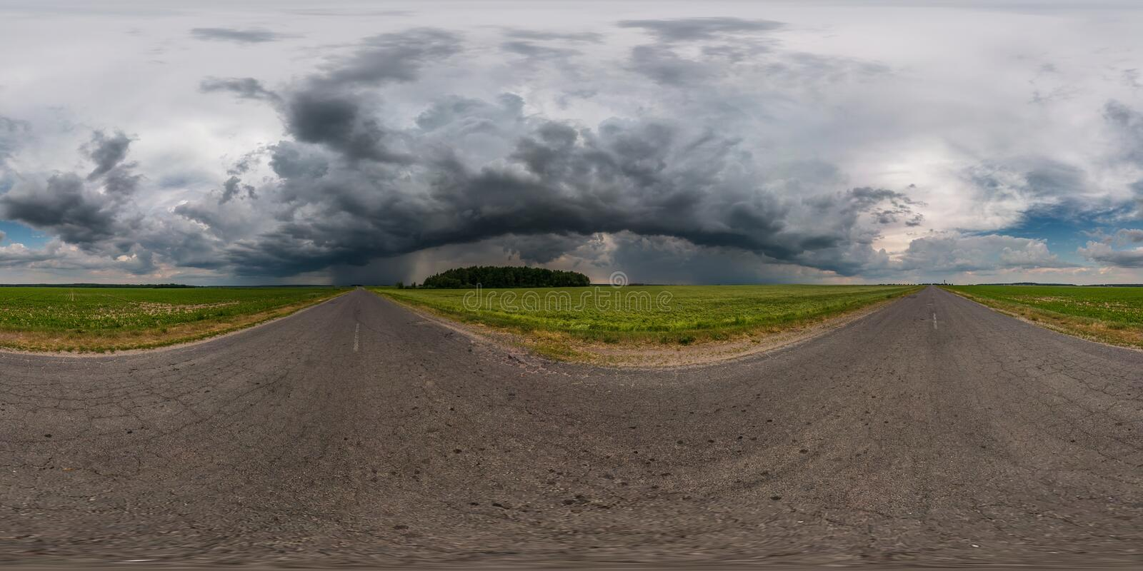 Full seamless spherical hdr panorama 360 degrees angle view on asphalt road among fields in evening with awesome black clouds. Before storm in equirectangular stock image