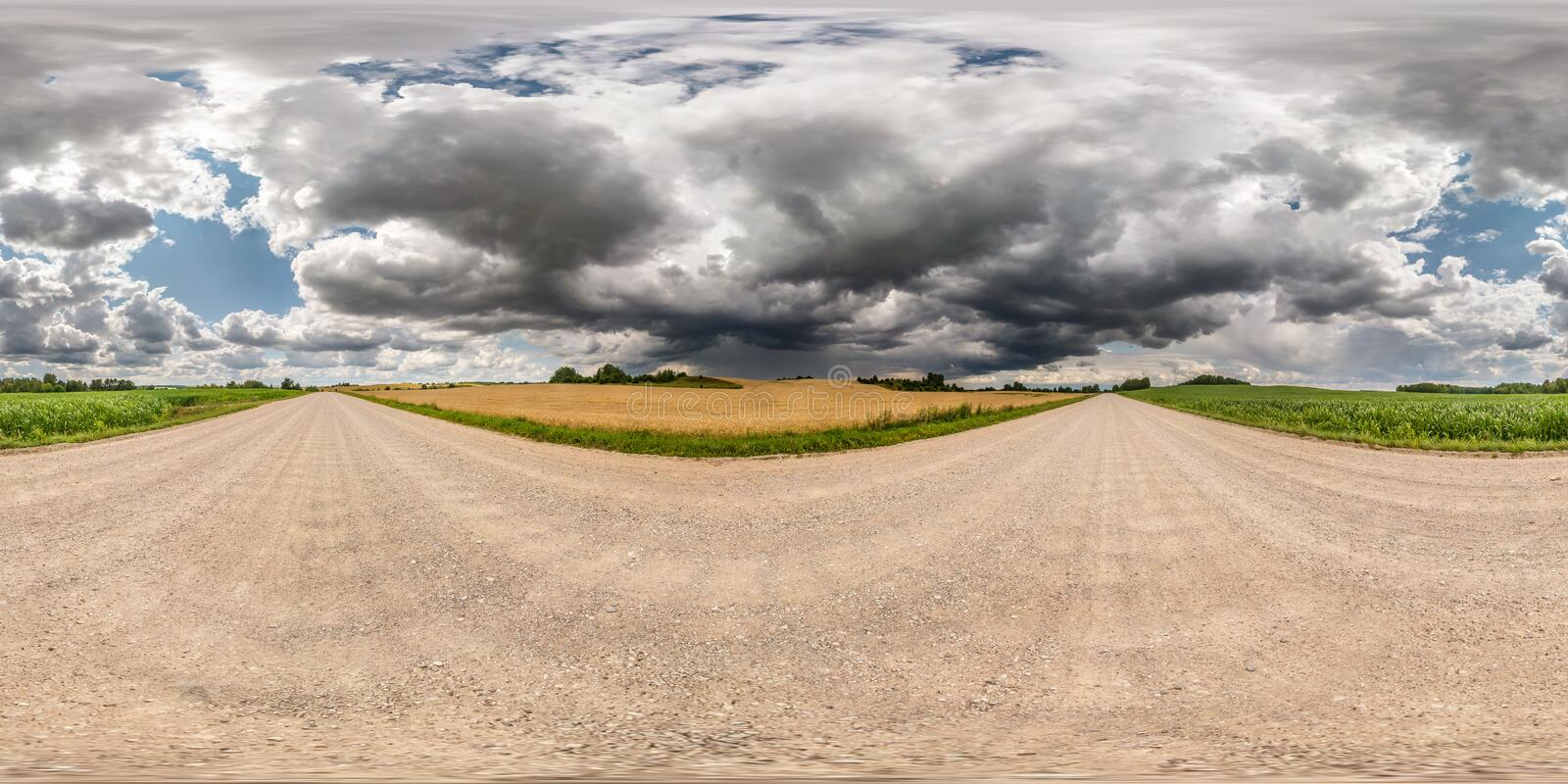 Full seamless spherical hdr panorama 360 degrees angle view on gravel road among fields with awesome black clouds before storm in. Equirectangular projection stock photography