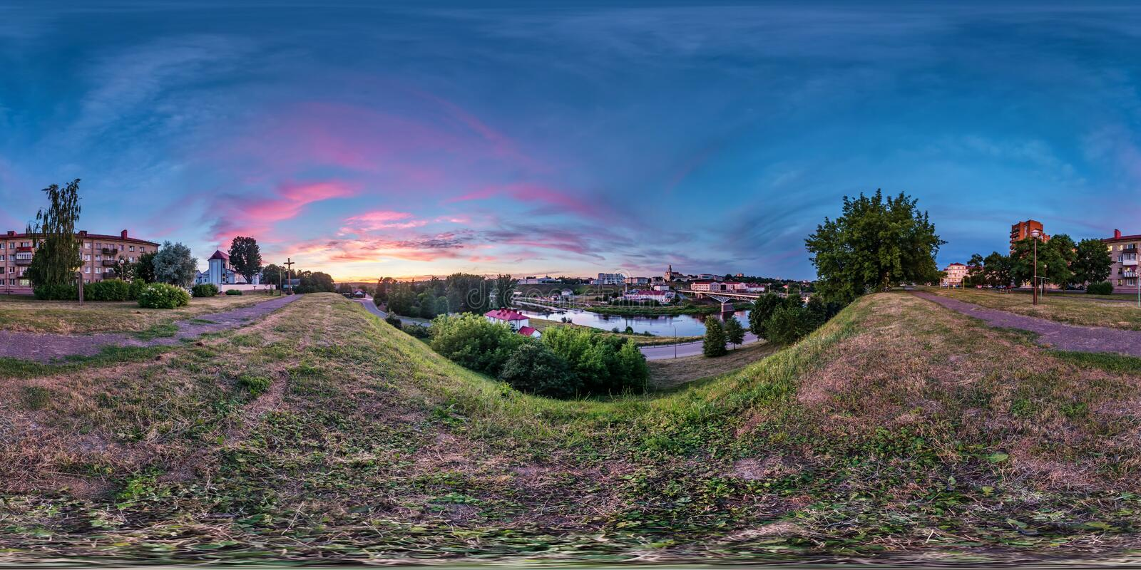 Full seamless spherical hdri panorama 360 degrees angle view on bank of wide river overlooking old city in sunset with beautiful. Clouds in equirectangular royalty free stock image