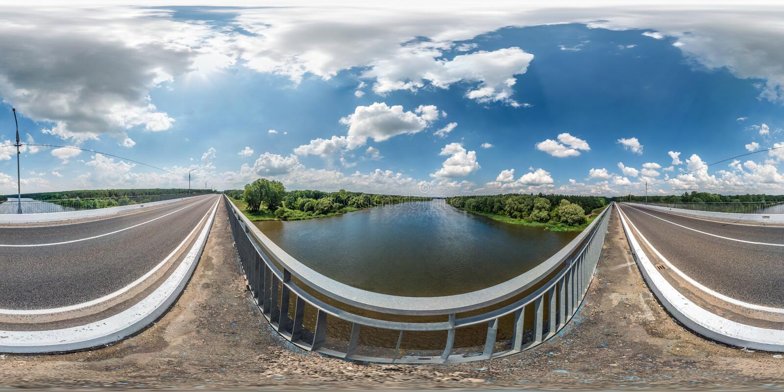 Full seamless spherical hdri panorama 360 degrees  angle view on concrete bridge near asphalt road across river in sunny summer. Day in equirectangular royalty free stock photo