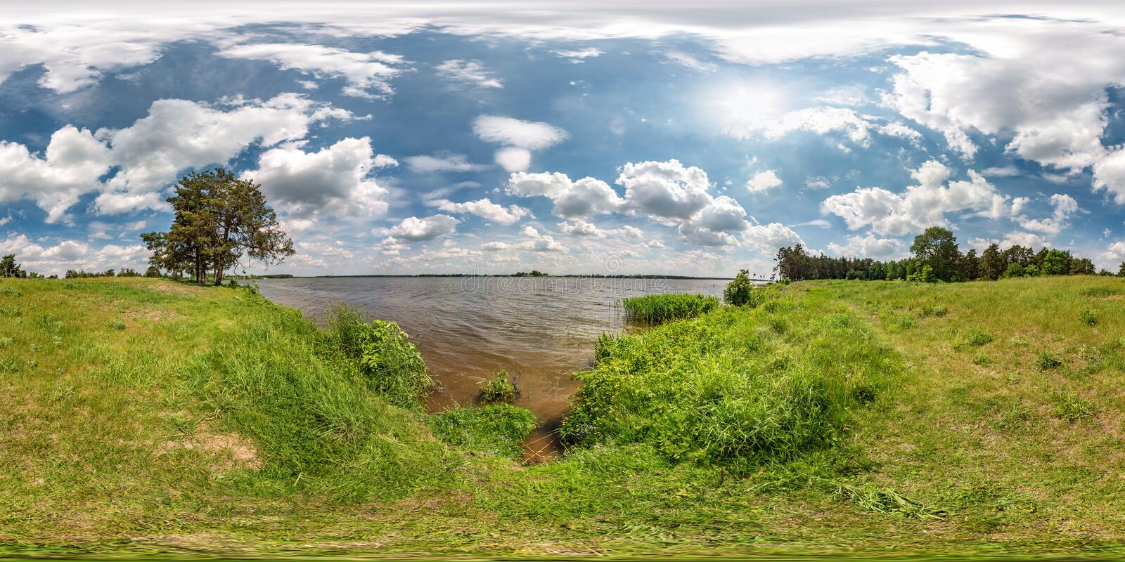 Full seamless spherical hdri panorama 360 degrees angle view on grass coast of huge lake or river in sunny summer day and windy. Weather with beautiful clouds stock images