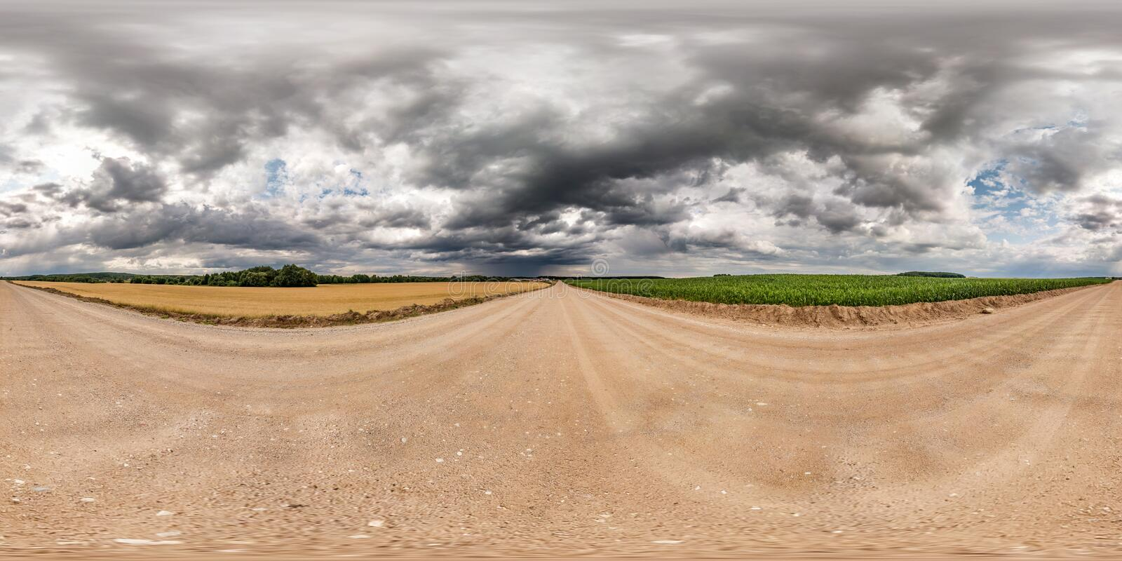 Full seamless spherical hdri panorama 360 degrees angle view on gravel road among fields with awesome clouds before storm in. Equirectangular projection, ready royalty free stock photography