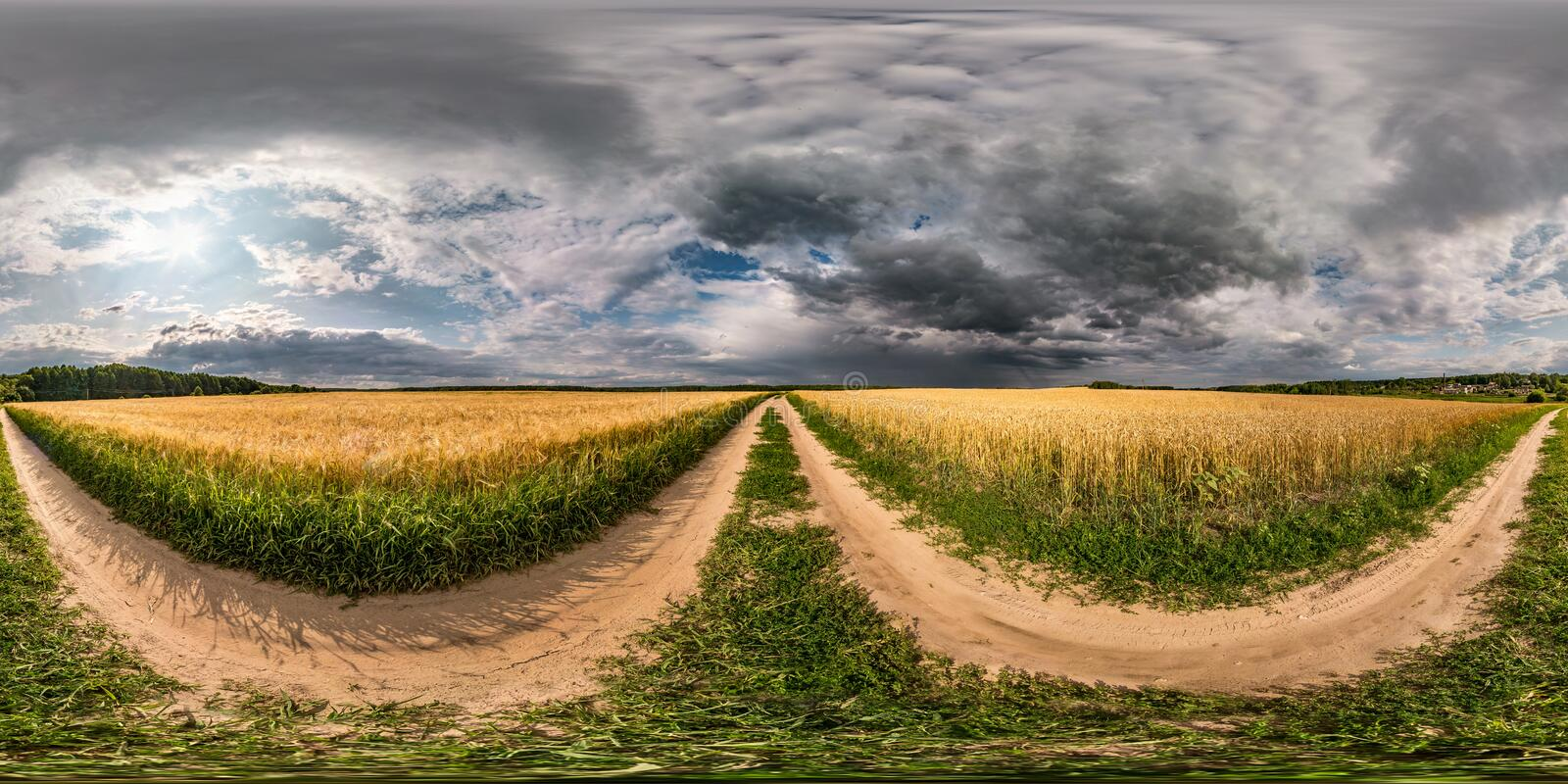 Full seamless spherical hdri panorama 360 degrees angle view on gravel road among fields with awesome clouds before storm in. Equirectangular projection with stock image