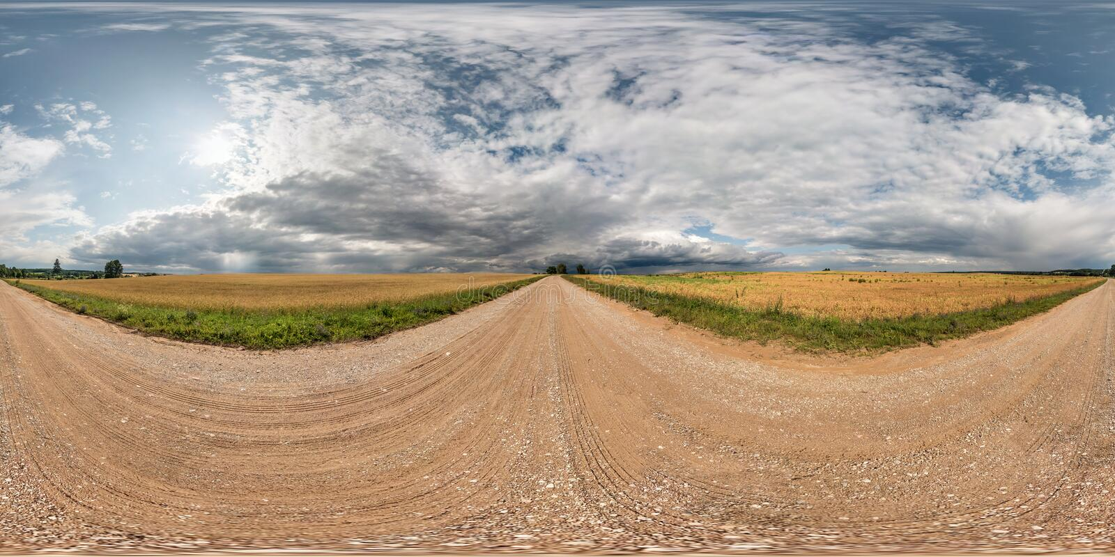 Full seamless spherical hdri panorama 360 degrees angle view on gravel road among fields with awesome clouds before storm in. Equirectangular projection, ready stock image